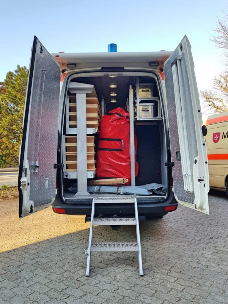Der Transporter des Malteser Betreuungsdienstes von Innen. Bänke, Tiche und ein großes Zelt – Foto: Nicole Stroschein